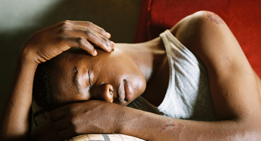 a women rests her head from the film Félicité.