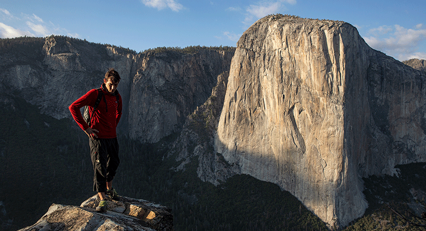 a man stands onto of a summit from the film Free Solo.