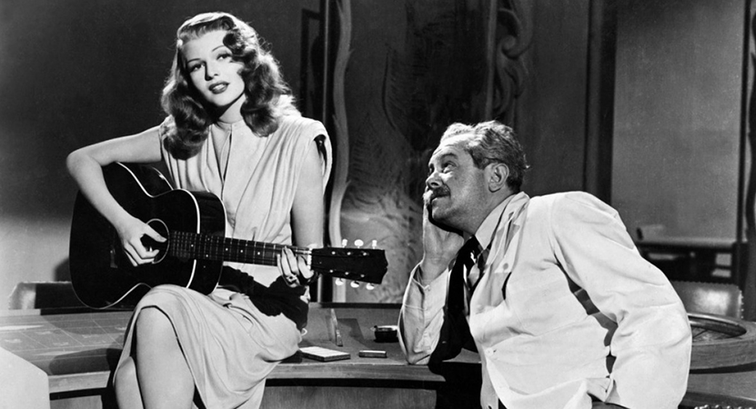 a women plays guitar while a man listens from the film Gilda.