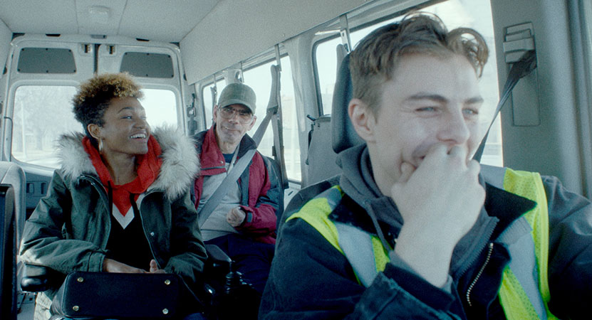 A group of people ride in a van from the film Give Me Liberty