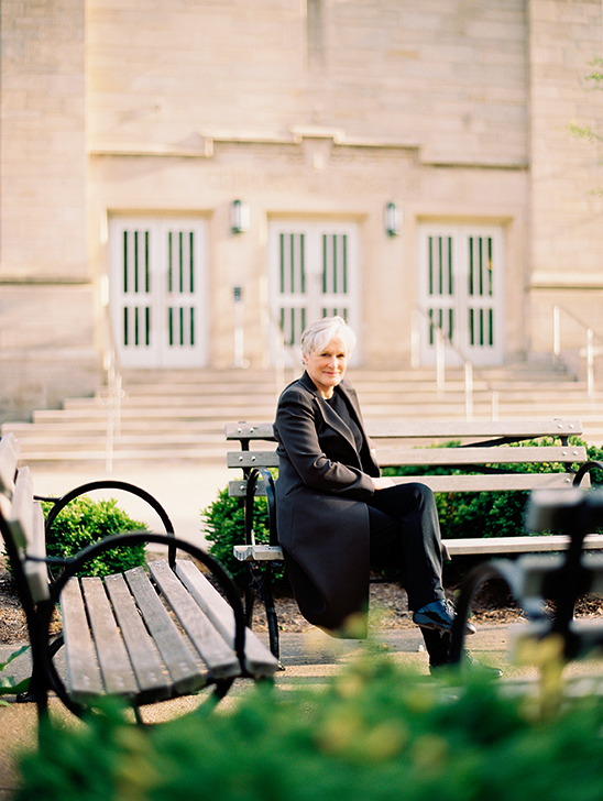 Glenn Close sits on a bench in front of IU Cinema.