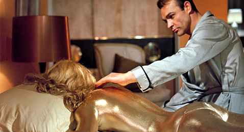 Still image or James Bond sitting on a bed next to a gold women from the film Goldfinger.