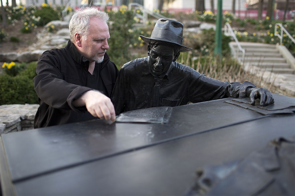 Guy Maddin sits by the hoagy statue in front of IU Cinema