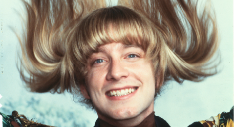 Still image of a man smiling from the film Hair.