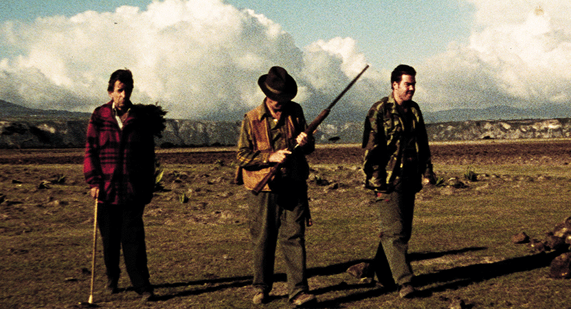 three men, one with a gun stand in the desert from the film Japón.