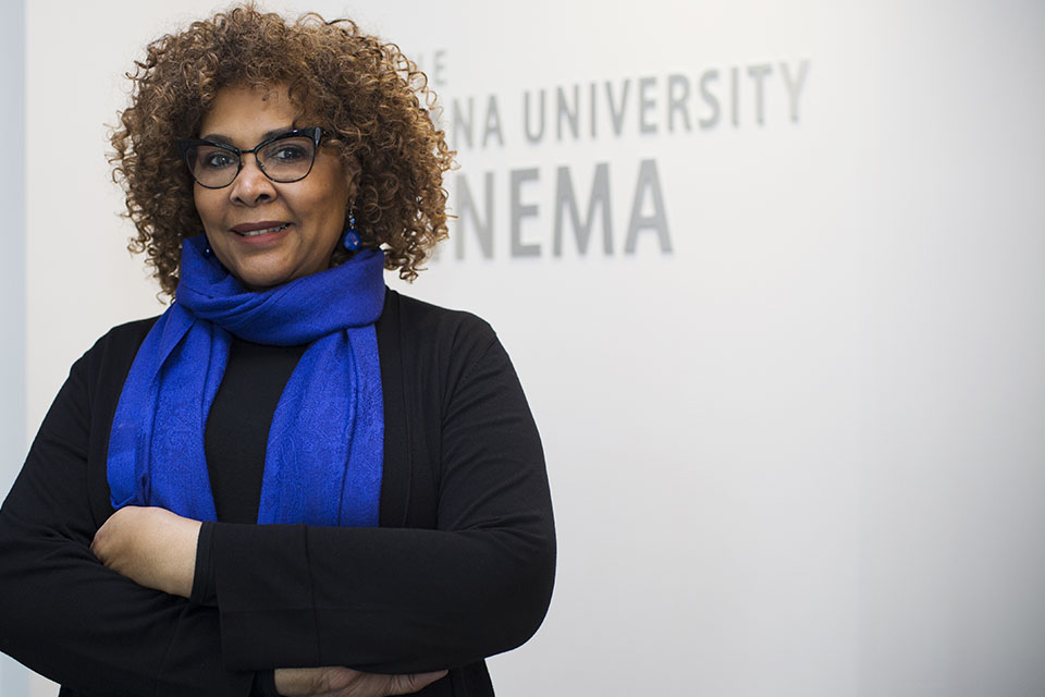 Julie Dash poses in front the the IU Cinema logo in the lobby of IU Cinema.