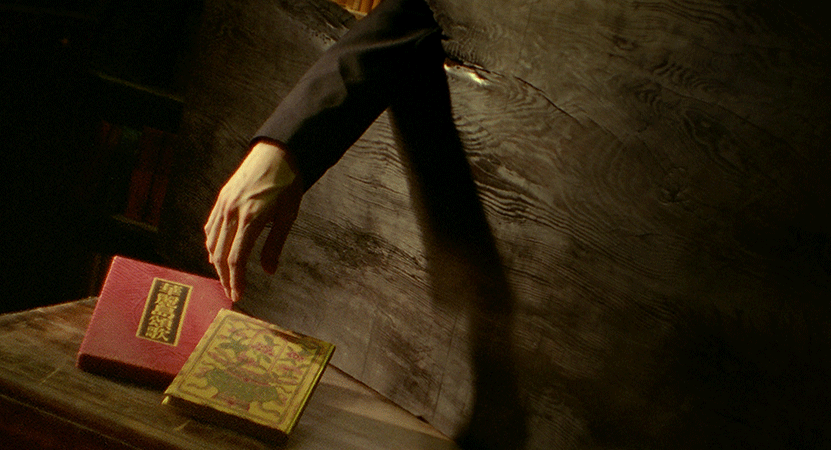 an arm reaches for a book from the film Le Moulin.