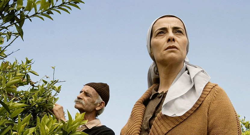 a man and women stand outside near a tree from the film Lemon Tree