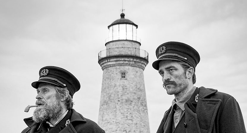 Two men stand in front of a brick lighthouse from the film The Lighthouse.