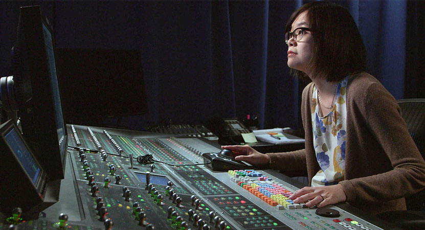 a women works at a sounds board from the film Making Waves: The Art of Cinematic Sound.