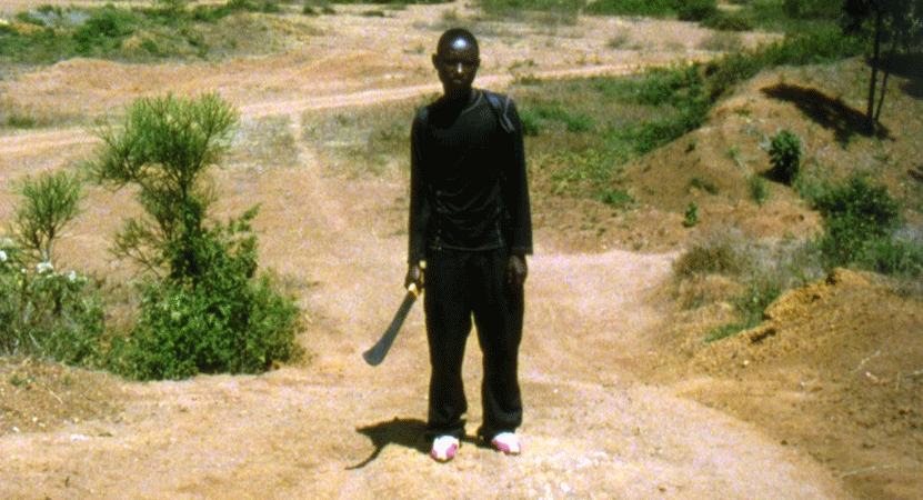 man stands with a machete from the film Munyurangabo.