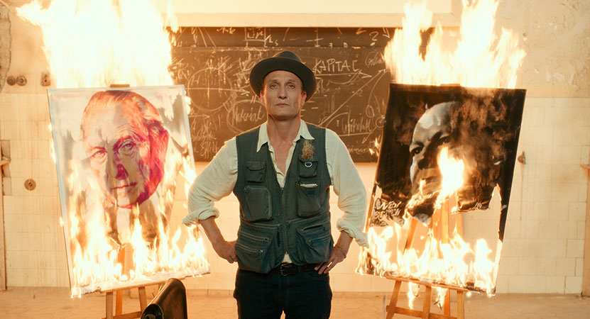 a man stands between two artworks on fire from the film Never Look Away