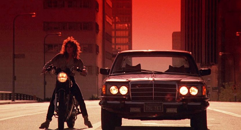 A women on a motorcycle sits next to a car from the film Night of the Comet