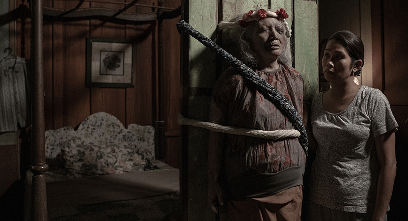 a women stands with a body tied to a post from the film Oda sa wala (Ode to Nothing)