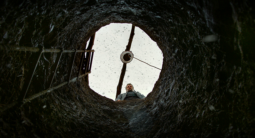 a man looks down a well from the film The Wild Pear Tree.