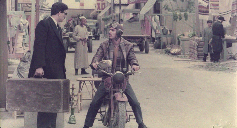 a man in a suit talks to a man sitting on a motorcycle from the film Za'am V'Tehilah (Rage and Glory).