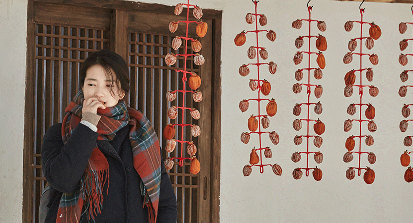 a young women stands outside from the film 리틀 포레스트 (Little Forest)