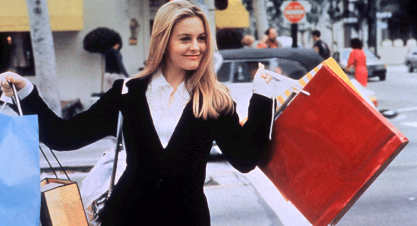 Cher (Alicia Silverstone) holds shopping bags from the film Clueless