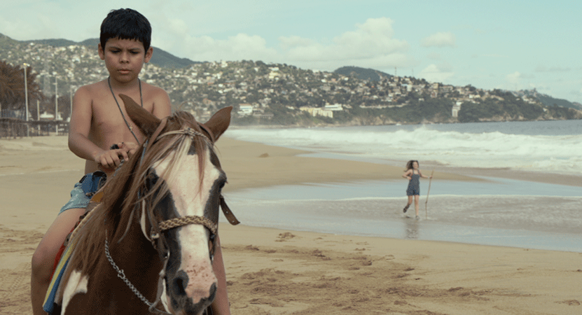 a boy rides a horse on a beach from the film Semana Santa.