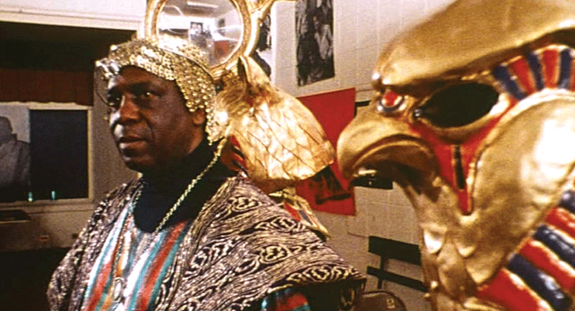 a man dressed in gilded cloths next to a hawk statue from the film Space is the Place.