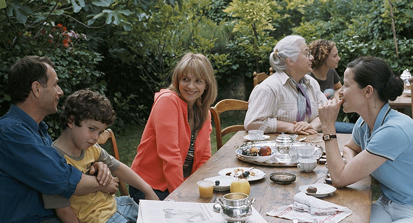 a group of people sit around a table outside from the film L'heure d'été (Summer Hours)