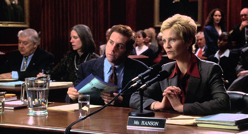 lawyers sit at a table in a court room from the film The Contender.