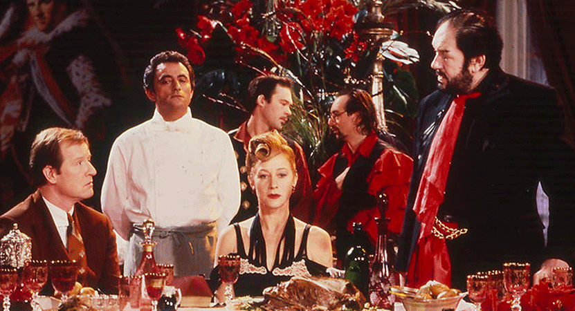 a group of people sit around a table from the film The Cook, the Thief, His Wife & Her Lover.