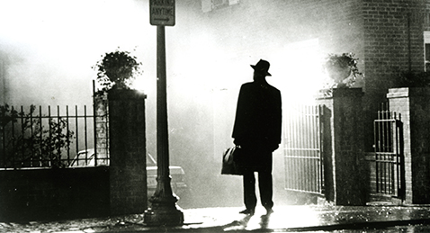 Still image of a man on a street corner form the film The Exorcist.