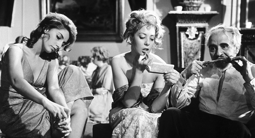 two women and a man sit eating from the film El ángel exterminador (The Exterminating Angel) .