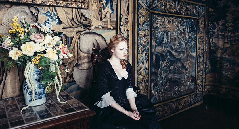 a women in victorian dress sits sits next to a table with flowers from the film The Favourite