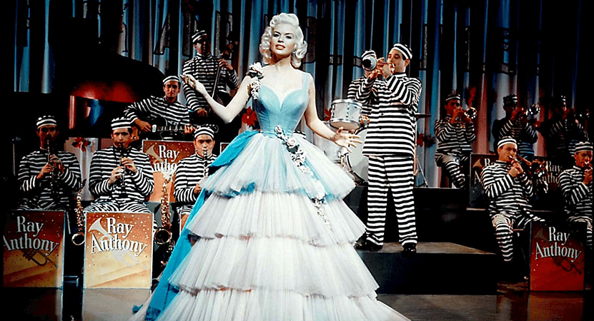 a women stands performing infront of a big band from the film The Girl Can't Help It