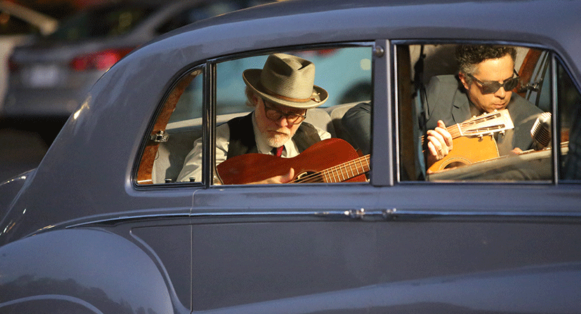 two men play guitar in a vintage car from the film The King.