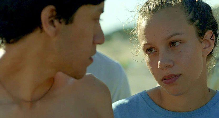 a young man and women look at each other form the film Los Tiburones (The Sharks)