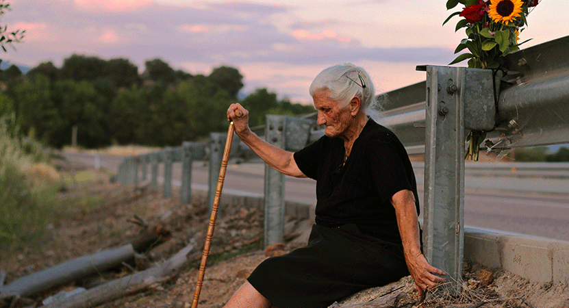 an elderly women sits by the road from the film The Silence of Others