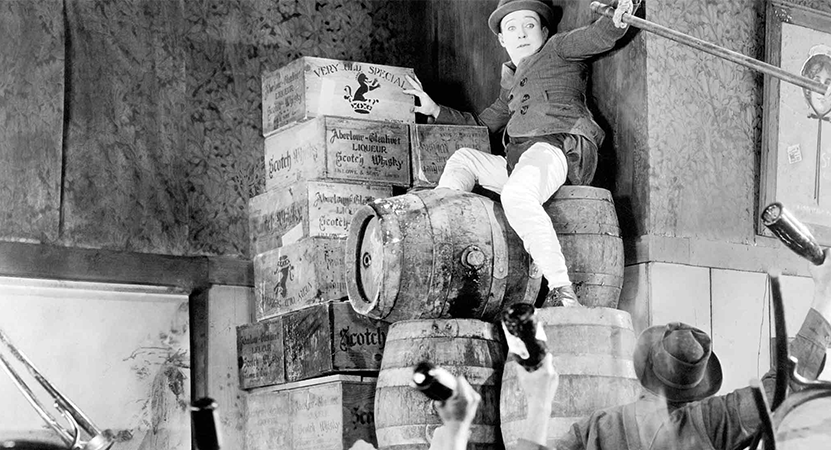 man trying to escape a crowed by climbing onto some barrels from the film The Strong Man.