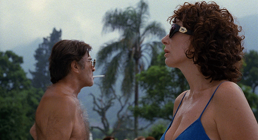 a man and a women stand in a tropical atmosphere from the film La Ciénaga (The Swamp)