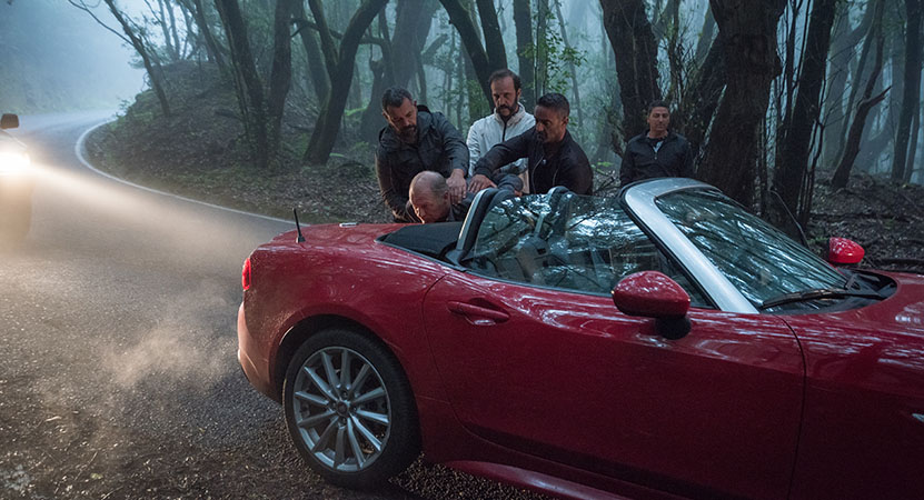 a group of men stand around a convertible from the film La Gomera (The Whistlers)