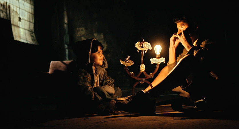 a man and child sit in a room with only a lamp to light the room from the film Vuelven (Tigers Are Not Afraid)