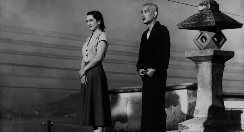 a man and women stand in front of a statue from the film Tokyo Story