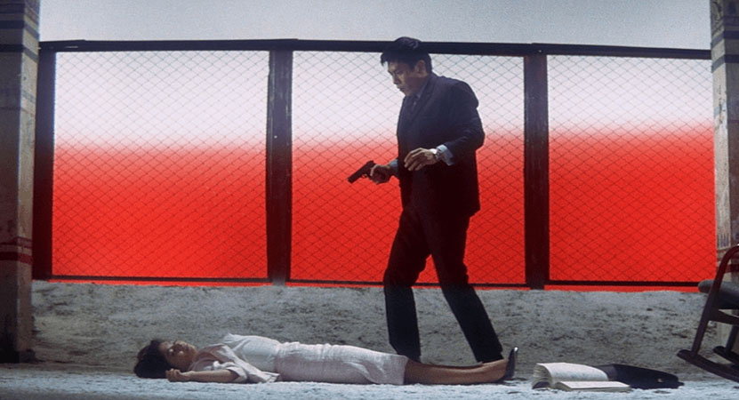 a man with a gun stands over a women from the film Tokyo Nagaremono (Tokyo Drifter)