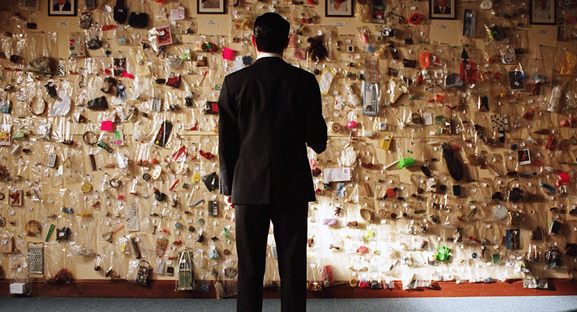 A man stands in front of a wall with notes and photos from the film Everything Is Illuminated.