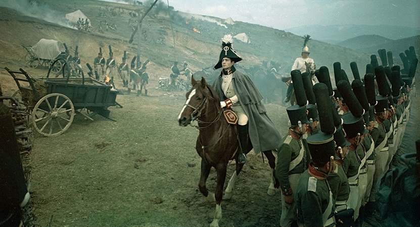 an officer rides a horse infront of his troops from the film War and Peace.