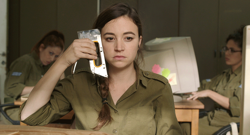 a girl holds a staple gun to her head in a classroom from the film Zero Motivation.