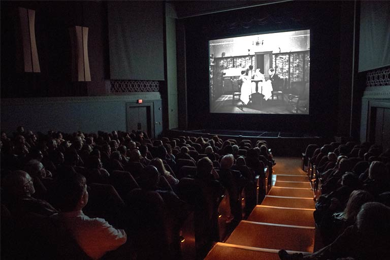 An audience watches a black and white film.