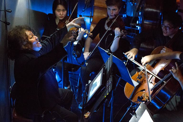 A conductor and musicians in an orchestra pit
