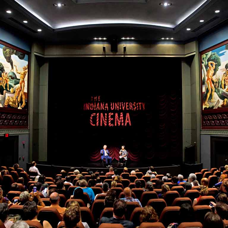 An audience listens to an interview. The words 'The Indiana University Cinema' are projected on the curtain.