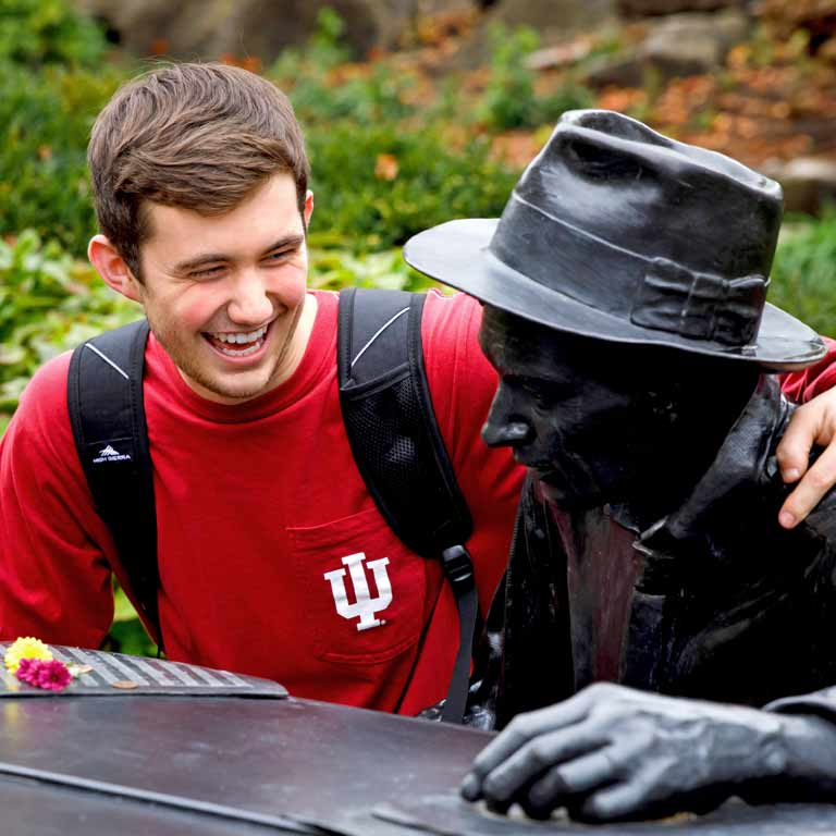 A student puts his arm around a bronze statue.